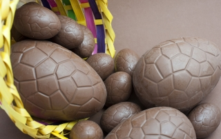 Assorted sized chocolate Easter eggs spilling out of a decorative wicker basket